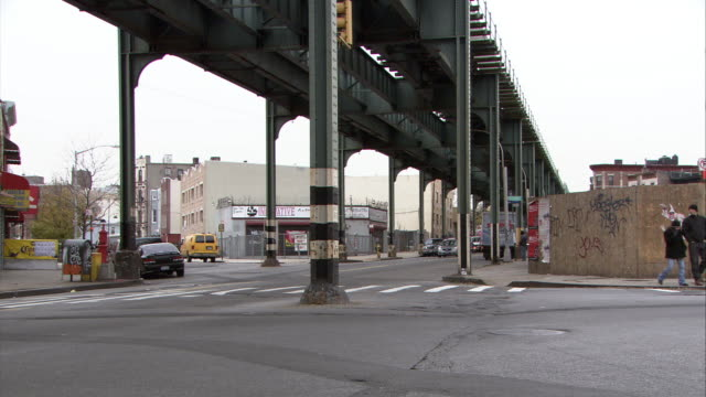 wide angle of new york city street corner under train bridge or railroad tracks. pedestrians visible. graffiti on walls. shops and storefronts. - corner stock videos & royalty-free footage