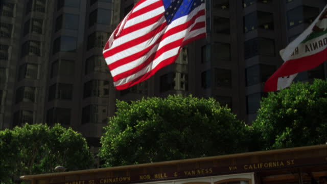 vídeos de stock e filmes b-roll de pan up from a cable car to a large american flag in front of an office building in a commercial area. could be trolley. - cable