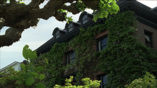 medium angle of an upper class two story house.  a brick building covered in ivy. the camera pushes in on the house. - nob hill stock videos & royalty-free footage