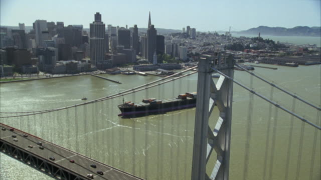 aerial of the downtown san francisco skyline as the camera flies over the bay bridge.  several cargo ships float underneath. - san francisco oakland bay bridge stock videos and b-roll footage
