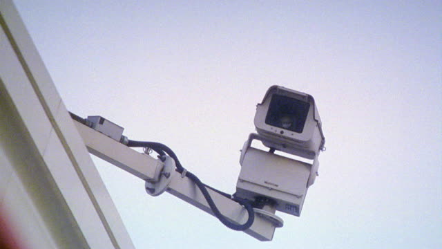 vidéos et rushes de close angle of a security camera attached to a metal pole mounted on a wall. cameras quickly pans away from then back to the security camera. - surveillance