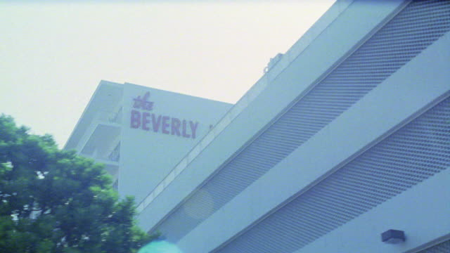 """medium angle driving pov straight right of multi-story upper class beverly hilton hotel. sign reading """"the beverly hilton"""" visible on side of building. palm trees. - the beverly hilton hotel stock videos & royalty-free footage"""