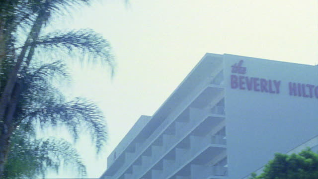 "stockvideo's en b-roll-footage met medium angle driving pov straight right of multi-story upper class beverly hilton hotel. sign reading ""the beverly hilton"" visible on side of building. palm trees. - beverly hilton hotel"