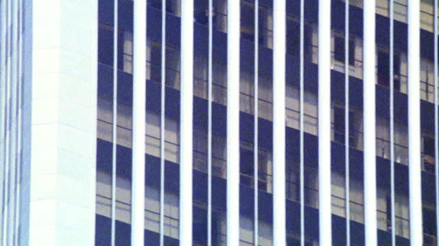 medium angle of windows of high rise office building. could be century plaza towers. camera pans to right past building and fronds of palm trees. glass buildings. - century city stock videos & royalty-free footage