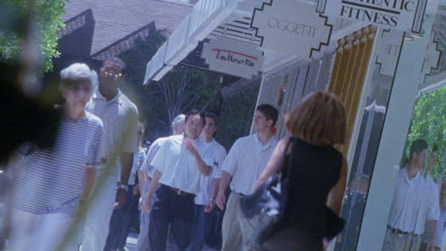 vidéos et rushes de medium angle of people walking in front of stores in an outdoor, upper class shopping center or shopping mall. - century city
