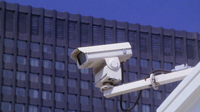 CLOSE ANGLE OF SECURITY CAMERA MOUNTED ON POLE ATTACHED TO WALL. SECURITY CAMERA PIVOTS LEFT AND RIGHT. HIGH RISE OFFICE BUILDING VISIBLE IN BG. SURVEILLANCE.