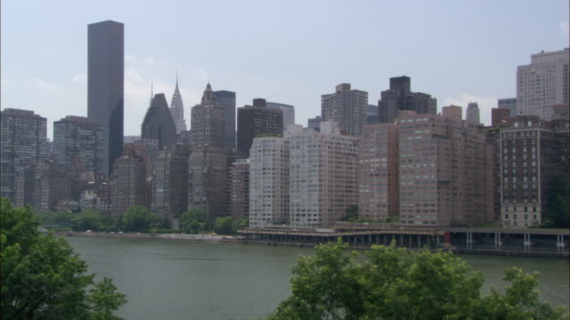 zoom in on the new york city skyline as seen from roosevelt island across the east river. the camera ends on the chrysler building. - 2007年点の映像素材/bロール