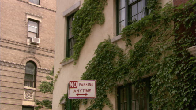 medium angle of an apartment building window in queens new york.  green ivy covers the white walls. - no parking sign stock videos & royalty-free footage