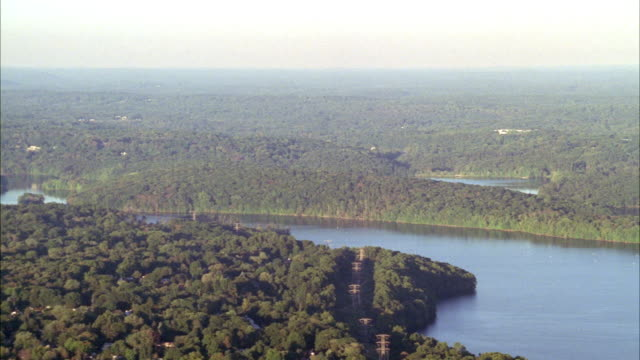 aerial over hudson valley in upper state new york. forest visible through hazy sky. pov pans to hudson river. trees. upper state new york. - hudson valley stock videos and b-roll footage