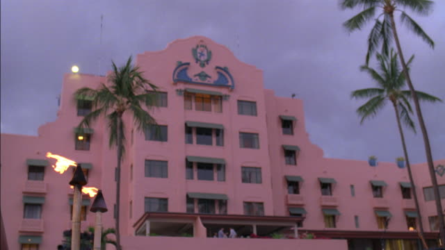 wide angle of multi-story luxury hotel, the royal hawaiian resort, with overcast or cloudy sky. spanish style architecture with awnings over room windows. - oahu stock videos and b-roll footage