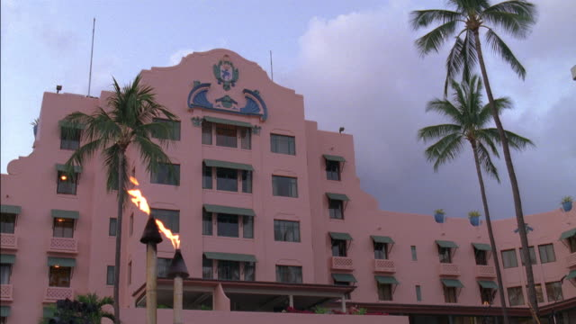 wide angle of multi-story luxury hotel, the royal hawaiian resort, with overcast or cloudy sky. spanish style architecture with awnings over room windows. - swimming trunks stock videos & royalty-free footage