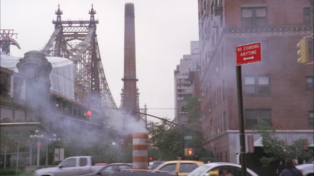 wide angle of a busy intersection in new york city. see smoke coming from a large orange and white tube. - cantilever bridge stock videos & royalty-free footage