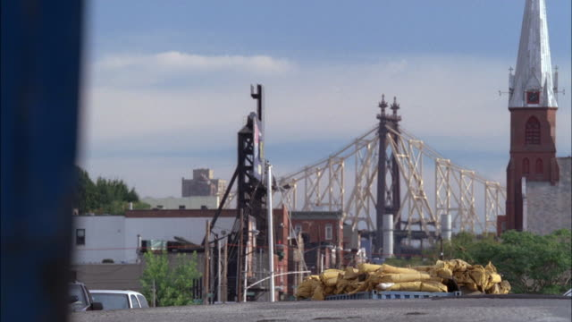 wide angle of a cantilever bridge in distance. see church steeple. multi-story brick building in background. a black sedan drives towards camera. new york city. - cantilever bridge stock videos & royalty-free footage