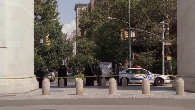 stockvideo's en b-roll-footage met wide angle of a police swat team underneath constantine arch in washington square park. swat team starts moving. - afzetlint