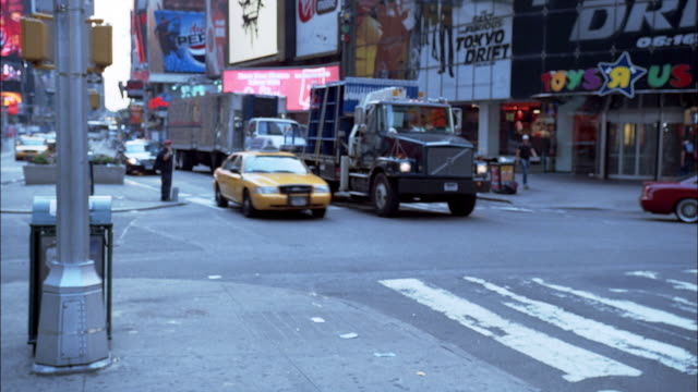 """WIDE ANGLE OF TIMES SQUARE. SEE TAXIS, TRUCKS, AND CARS DRIVING THROUGH INTERSECTION. SEE SEVERAL BILLBOARDS AND STORES. SEE LIGHTED MARQUEE FOR A """"SUPERMAN"""" MOVIE."""