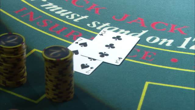 close angle on a stack of chips on a blackjack table. the dealer places two cards on the table, and then another card for a total of 17. the dealer takes away the chips, and the player loses. - blackjack stock videos and b-roll footage