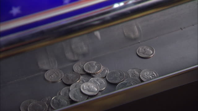 CLOSE ANGLE OF QUARTERS FALLING ON THE BOTTOM OF A SLOT MACHINE.  WINNING GAMBLING AT A CASINO.