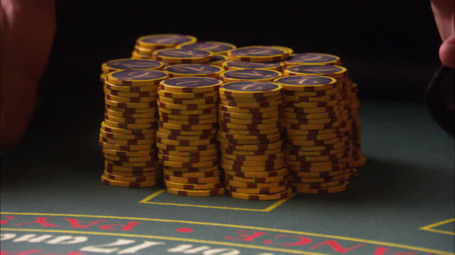 CLOSE ANGLE OF CASINO CHIPS PILED ON CASINO TABLE. MAN IN A SUIT RUNS HANDS THROUGH CHIPS AND KNOCK THEM OVER THE TABLE. COULD BE USED FOR WINNING THE JACKPOT IN A HIGH STAKES GAME. MONEY. GAMBLING.