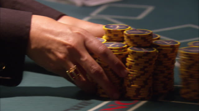 stockvideo's en b-roll-footage met close angle of casino chips on blackjack table. dealer passes stacks of chips to player. player then runs hands through stacks creating a pile of chips on the table. could be used for winnings in a high stake game. gambling. - gokken