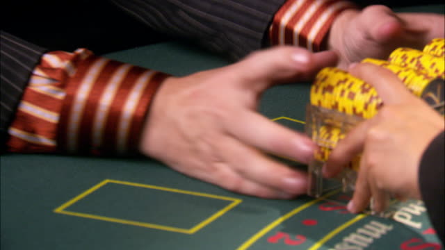 close angle of casino chips in trays passed back and forth between dealer and player. player in a suit taps his fingers anticipating chips from dealer. - winnings stock videos and b-roll footage