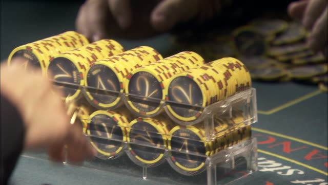 close angle of casino chips on blackjack table. dealer passes trays of chips to player adding to a pile of chips already on table. could be used as winnings in a high stake game. gambling. - winnings stock videos and b-roll footage