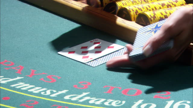 close angle of blackjack table. woman deals cards to players and house wins. casino chips and money visible on table. gambling. - blackjack video stock e b–roll