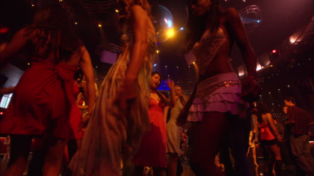 WIDE ANGLE UP OF WOMEN AND MEN DANCING ON DANCE FLOOR. CLUB'S FLASHING LIGHTS REFLECT OFF WALLS AND FLOOR. MIRRORED DISCO BALL VISIBLE ON CEILING.
