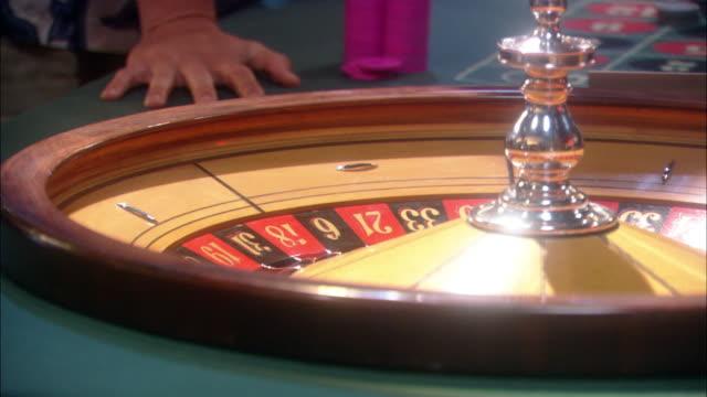 vídeos de stock, filmes e b-roll de close angle of roulette wheel on casino table shows hand of croupier, dealer place ball and spin wheel. gambling. - jogo da sorte