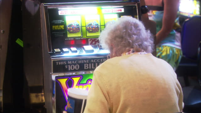 medium angle of elderly woman sitting at slot machine, seen from the back.  woman is shaking tub of coins, looking up at machine as if yelling at it. elderly people. gambling. - casino stock videos & royalty-free footage