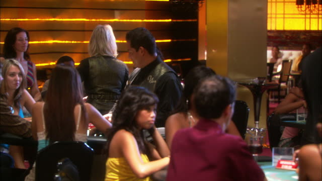 medium angle of gamblers seated around casino table with dealer dealing cards, could be blackjack. pit boss seen behind dealer. - blackjack stock videos and b-roll footage