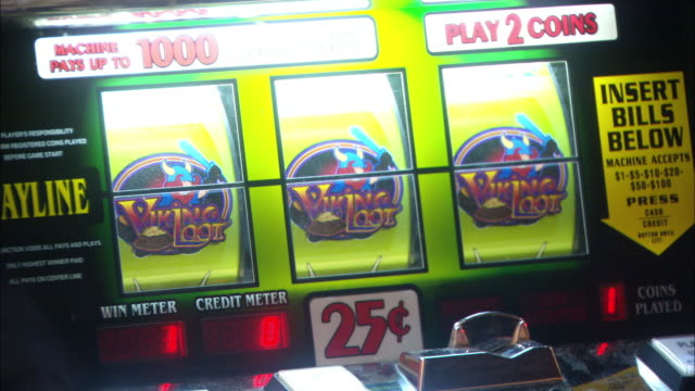 CLOSE ANGLE OF SPINNING SLOT MACHINE REELS AS THEY STOP ON THREE OF A KIND, WINNING JACKPOT. PANS DOWN TO SHOW COINS FALLING INTO TRAY AS ELDERLY WOMAN SCOOPS OUT MONEY. GAMBLING.