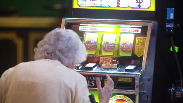 vídeos y material grabado en eventos de stock de medium angle of elderly woman sitting at slot machine in casino. woman shakes hands as if she has won. gambling. people. - tragaperras