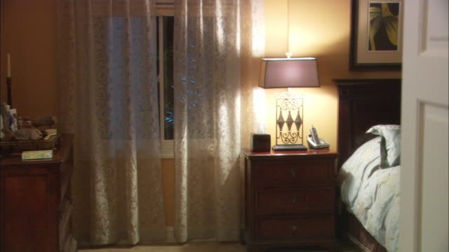 vídeos de stock, filmes e b-roll de pull back from medium angle of woman's bedroom with lace curtains, bureau and bed through interior doorway. - quarto de dormir