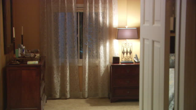 medium angle of woman's bedroom with lace curtains, bureau and bed seen through interior doorway. - bedroom doorway stock videos & royalty-free footage