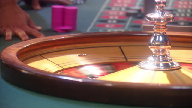 vídeos de stock, filmes e b-roll de pan right to left then back repeatedly shows croupier's hands spin roulette wheel then pass stacks of chips to gambler who throws chips into air. - jogo da sorte