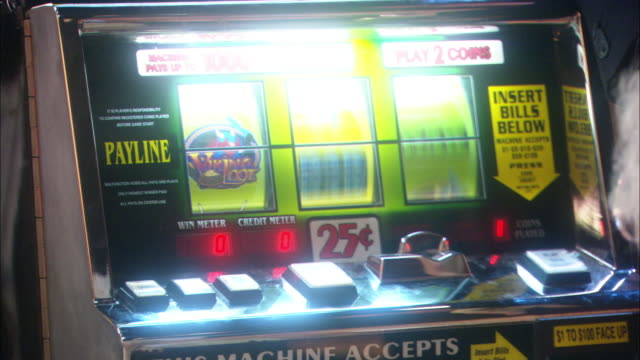 PAN RIGHT TO LEFT SHOWS ELDERLY WOMAN GAMBLING AT SLOT MACHINE HIT JACKPOT. PANS DOWN TO SHOW COINS POURING INTO TRAY. PEOPLE.