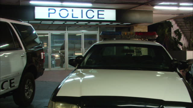 MEDIUM ANGLE OF ENTRANCE TO POLICE STATION WITH POLICE CARS PARKED IN FRONT. PANS RIGHT SHOWING OFFICERS IN FRONT OF STATION, PANS BACK TO START AS CAR BACKS THROUGH DRIVEWAY.
