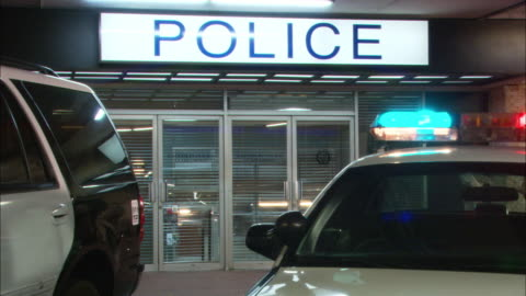 pan left to right shows entrance to police station with police cars parked in front, bizbars, sirens and lights flashing. - nevada stock videos & royalty-free footage