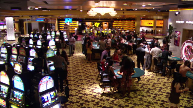 vídeos de stock, filmes e b-roll de wide angle of casino interior with men and women walking about, gambling, and talking. slot machines, craps tables, roulette wheels all present. bar in background. - cassino