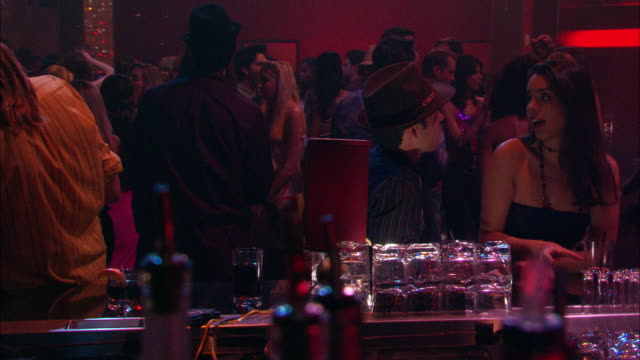 medium angle of man and woman talking, flirting, drinking cocktails at bar in dance club, nightclub. people dance in background. alcohol. couples. - bar video stock e b–roll