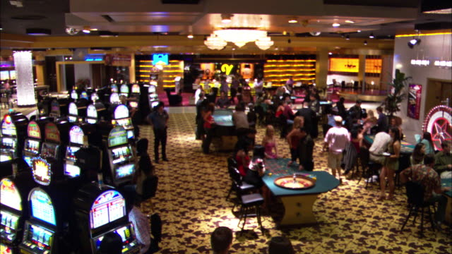 wide angle of casino interior with men and women walking about, gambling, and talking. slot machines, craps tables, roulette wheels all present. bar in background. - craps stock videos & royalty-free footage