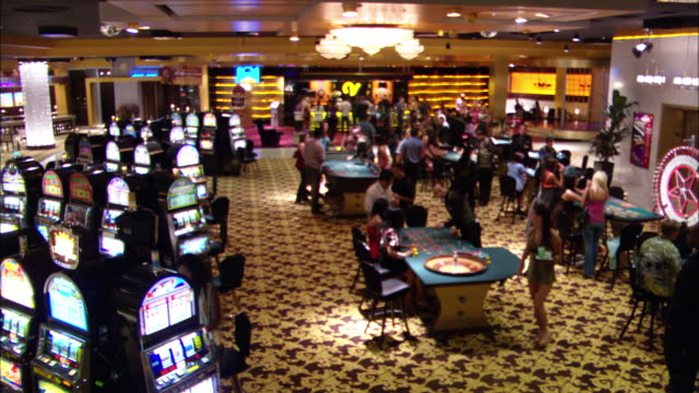 wide angle of casino interior with men and women walking about, gambling, and talking. slot machines, craps tables, roulette wheels all present. bar in background. - roulette stock videos & royalty-free footage