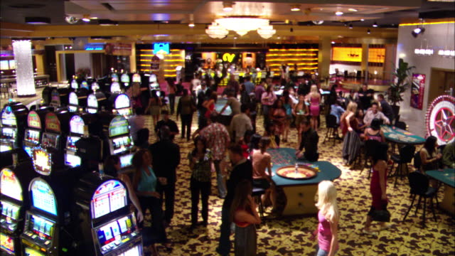 wide angle of casino interior with men and women walking about, gambling, and talking. slot machines, craps tables, roulette wheels all present. bar in background. - kasino stock-videos und b-roll-filmmaterial