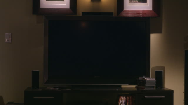 medium angle of a blank flat screen sony television screen sitting on a desk. two matching picture frames visible above. could be computer monitor. could be in den, family room, or home office. - picture frame stock videos & royalty-free footage