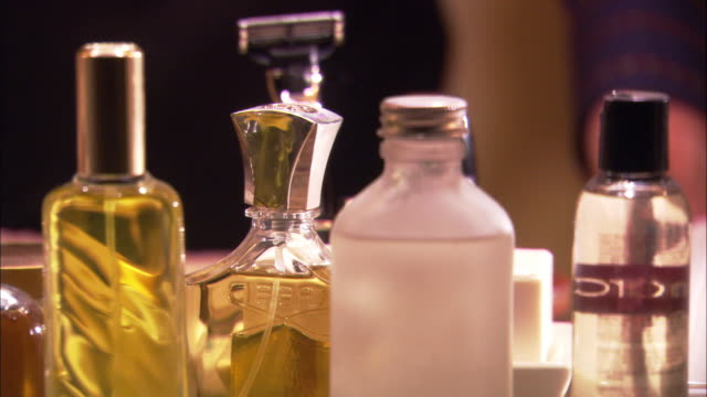 CLOSE ANGLE OF MEN'S FRAGRANCES IN FRONT OF MIRROR. SEE MAN REACHING FOR BOTTLES. RAZOR BLADES AND OTHER TOILETRIES VISIBLE THROUGHOUT.