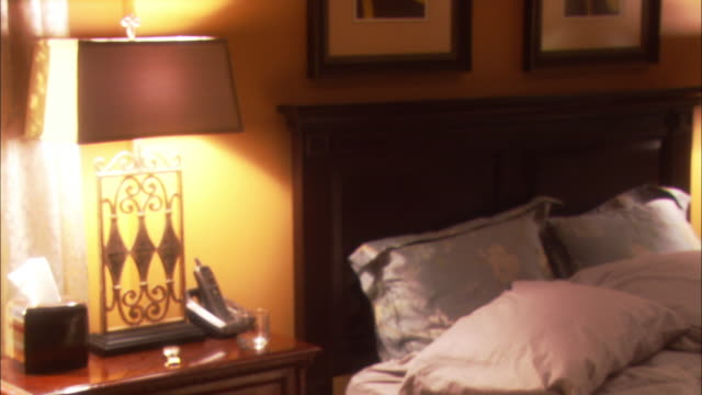 medium angle of bedroom. bed has comforter and pillows. end table has lamp cordless phone and tissue box. framed art posted above wooden bed frame. - cordless phone stock videos and b-roll footage