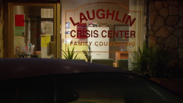 MEDIUM ANGLE OF 'LAUGHLIN CRISIS CENTER FAMILY COUNSELING' FROM PARKING LOT. LIGHTS ARE TURNED ON IN OFFICE BUILDING.