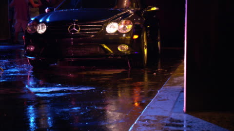 medium angle zoom in of black mercedes pulling up to a sidewalk. car stops and door opens. flashing lights from building reflect off car. escorts. groupies. - mercedes benz markenname stock-videos und b-roll-filmmaterial