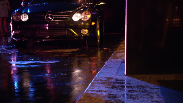 medium angle zoom in of black mercedes pulling up to a sidewalk. car stops and door opens. flashing lights from building reflect off car. - mercedes benz stock videos and b-roll footage