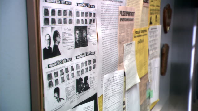 "close angle of bulletin board covered with flyers. one flyer reads ""wanted by fbi"" and features fingerprints and mug shot photos of criminals. - criminal stock videos & royalty-free footage"